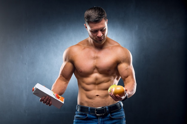 Bodybuilder sportsman holding fruits and juice.