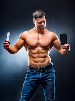 Bodybuilder sportsman holding sport bar and chocolate . choosing between healthy and harmful food. naked torso. grey background. vertical photo. closeup