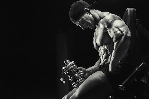Культурист сильный спортивный грубый мужчина пьет воду после тренировки, фитнеса и бодибилдинга