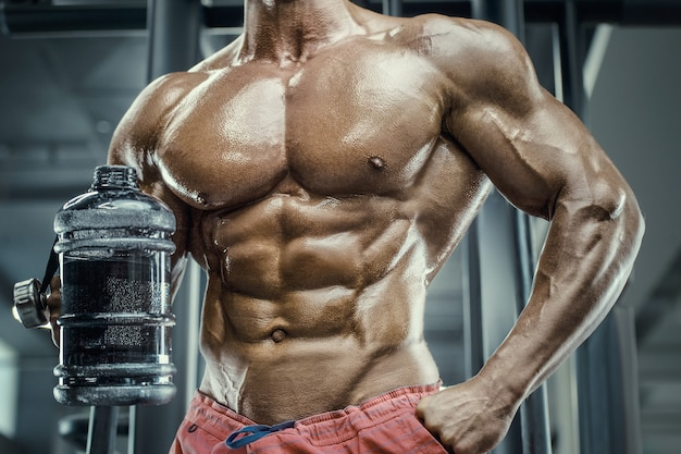 Bodybuilder strong athletic rough man drinking water after workout workout fitness and bodybuilding healthy concept