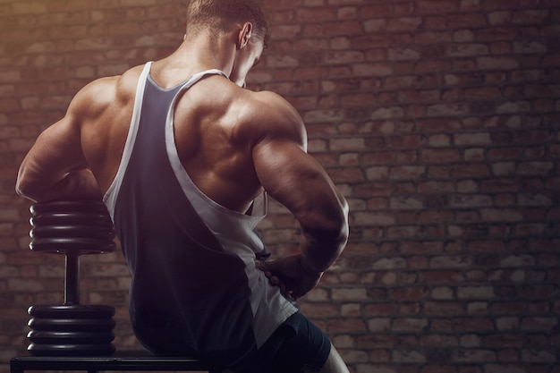 Bodybuilder strong man pumping up back muscles