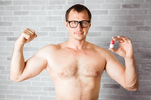 ボディービルダーは、筋肉の発達の急速な進歩の製薬の錠剤の形でドープを取ります