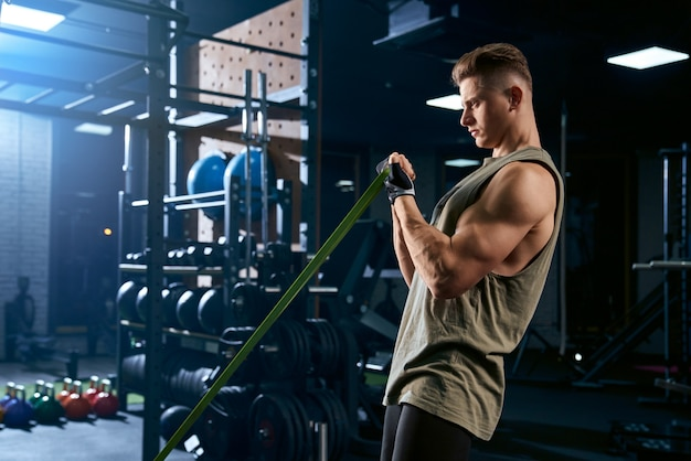 Bodybuilder training arm with resistance band.