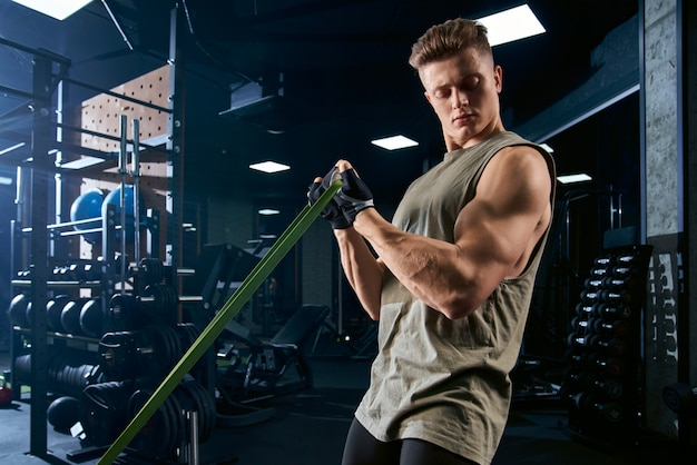 Bodybuilder training biceps with resistance band.