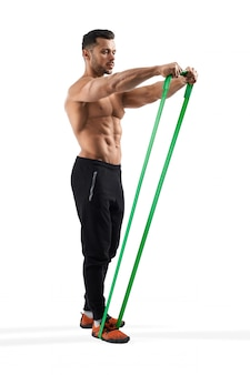 Bodybuilder training shoulders using resistance band.