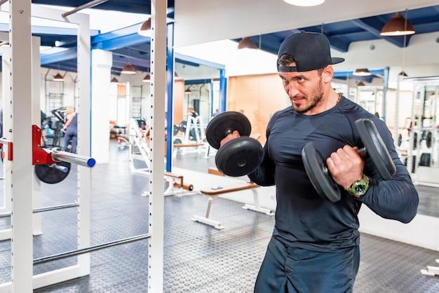 ボディービルダーはダンベルで上腕二頭筋を訓練します。フィットネスとクロスフィットのコンセプト。閉じる