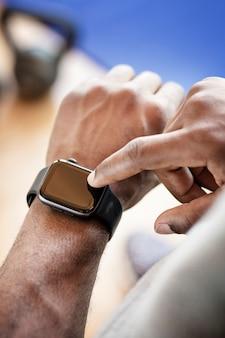 Bodybuilder using a smartwatch
