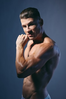 Bodybuilder with pumped up arm muscles smiling isolated