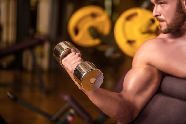 Бодибилдер работает с гантелями в тренажерном зале. человек, снимающий гантели в тренажерном зале, делая упражнения для мышц. культурист человек делает упражнения с гантелями. человек фитнеса подъема гантелей