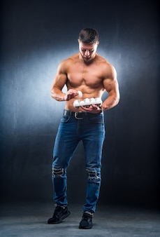 Bodybuilder young sportsman is holding a packaging with eggs