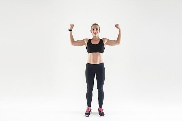 ボディービルのコンセプト。パワフルで魅力的な筋肉質の女の子がフィットネスに従事しました。カメラで上腕二頭筋を見せて笑っている女性。スタジオショット、灰色の背景