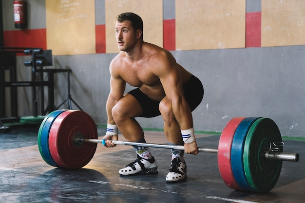 Bodybuilding concept with man in gym lifting barbell