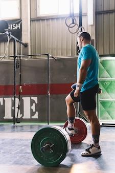 Концепция бодибилдинга с человеком, держащим ногу на штанге