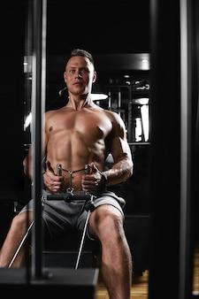 ボディービルのフィットネスの動機は、ジムの男がトレーニングしている美しい体を構築します