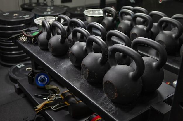 ボディービル、フリーウェイト機器。モダンなジムにあるケトルベルとフィットネスアクセサリーを備えたラック。ファンクショナルトレーニング