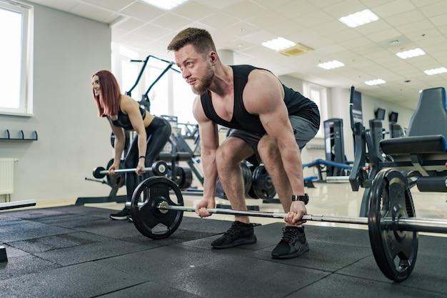 ボディービル。ダンベルで運動する強いフィットの男。ジムでウェイトリフティングの筋肉の少年。 Premium写真