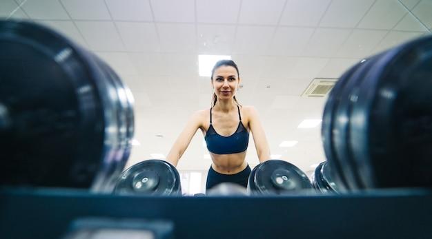 ボディービル。ダンベルで運動する強いフィットの女性。ジムでウェイトリフティング筋肉のブロンドの女の子。