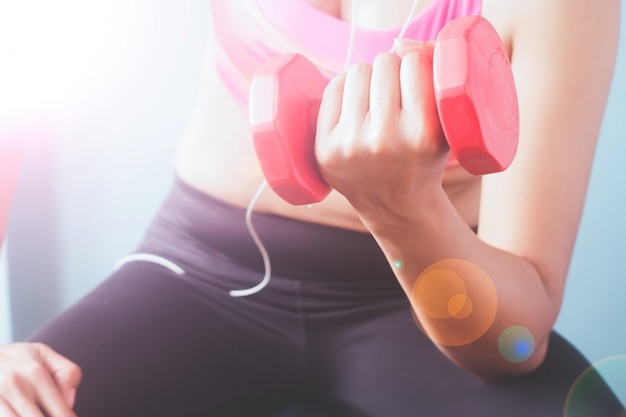 ボディービルディング。赤いダンベルでエクササイズするピンクスポーツブラジャーにフィットする女性。