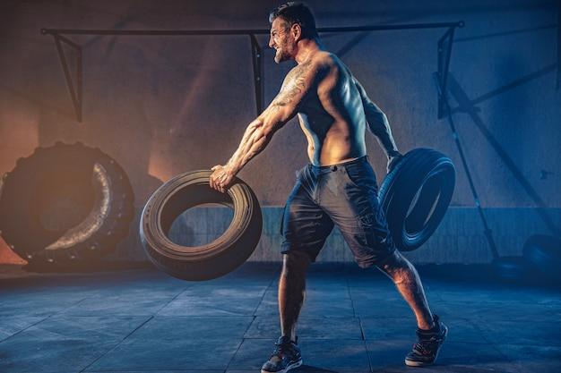Бодибилдинг, бородатый сильный спортсмен с мускулистым телом, поднимающий тяжелое колесо в тренажерном зале.