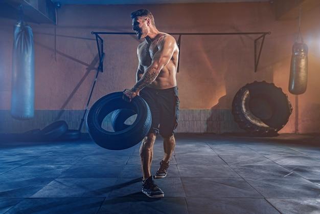 ボディービルのトレーニング、ジムで重いホイールを持ち上げる筋肉質の体を持つひげを生やした強いスポーツマン。