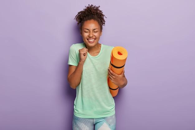 ボディケアとスポーツのコンセプト。エネルギッシュな嬉しい暗い肌の女性は喜びで拳を食いしばる