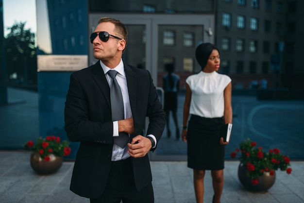 Bodyguard in suit and sunglasses, female vip client