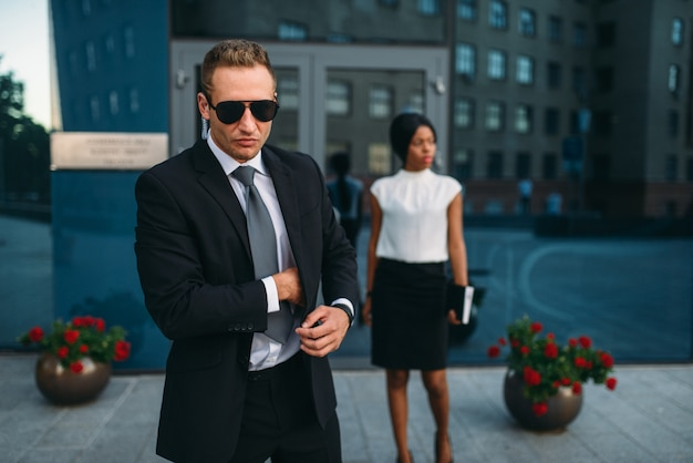 Bodyguard in suit and sunglasses, female vip