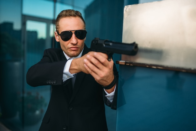 Bodyguard in suit and sunglasses with gun in hands
