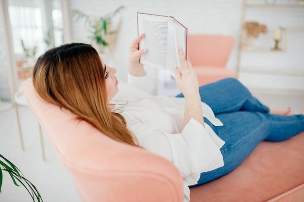 白いシャツとジーンズのbodypositive若い女性は、自宅の明るく居心地の良い部屋のベッドに横たわっている間本を読みます。ホームスクーリング