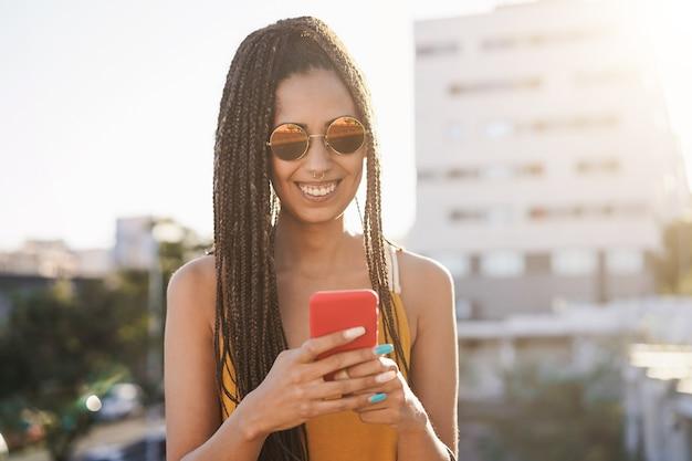 백그라운드에서 도시와 야외 휴대 전화를 사용하는 보헤미안 아프리카 소녀 - 얼굴에 초점