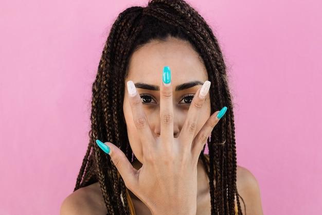 긴 아크릴 손톱으로 손을 보여주는 동안 카메라를 보고 있는 보헤미안 소녀 - 손에 주요 초점