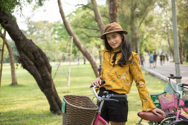 Bohemian girl with bike in summe park