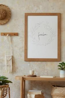 포스터 프레임, 우아한 등나무 액세서리, 식물, 나무 콘솔 및 세련된 가정 장식에 매달려있는 오두막이있는 거실의 보헤미안 인테리어.