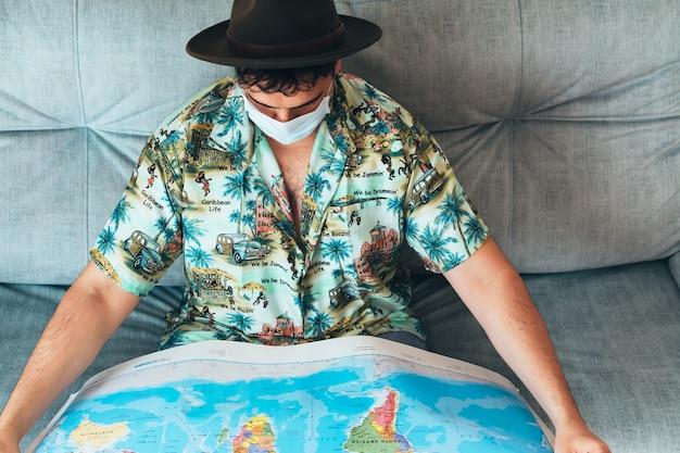 그의 얼굴에 마스크와 그의 소파에 세계의지도를보고 모자 보헤미안 남자. 하와이안 셔츠와 청바지를 입고. 다시 여행 할 새로운 목적지를 선택합니다. 코로나 바이러스 감염병 세계적 유행