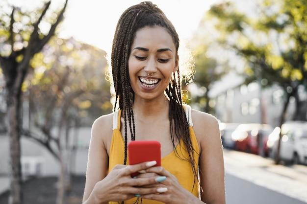 백그라운드에서 도시와 야외 휴대 전화를 사용하는 보헤미안 혼혈 소녀 - 얼굴에 초점