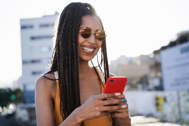 도시를 배경으로 야외에서 스마트폰을 사용하는 보헤미안 혼혈 소녀 - 기술 및 트렌디한 라이프스타일 개념 - 얼굴에 집중 프리미엄 사진