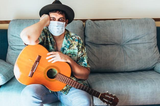 Богемский музыкант с маской на лице и шляпе играет на испанской гитаре с дивана. одета в гавайскую рубашку и джинсы. концептуальная музыка из дома во время заключения. коронавирус пандемия.