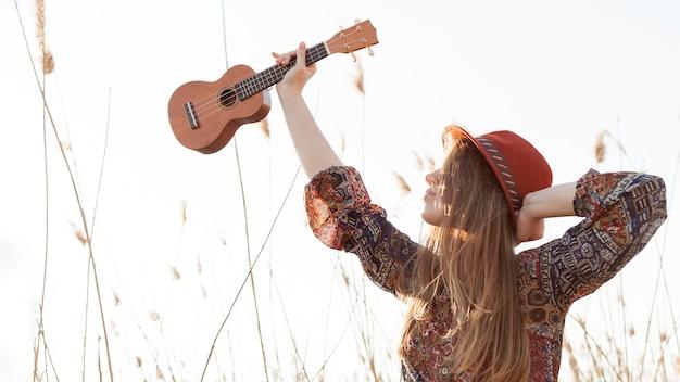 Богемная женщина держит гавайскую гитару и позирует