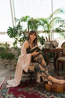 スタイリッシュなリビングルームで本を読んでエレガントなホームウェアのボヘミアン女性。
