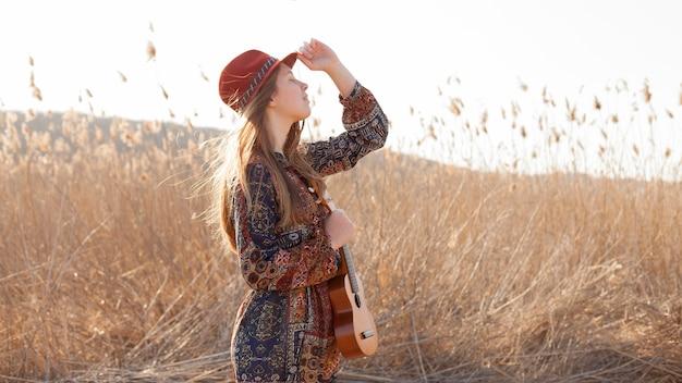 Богемная женщина в поле держит гавайскую гитару