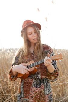 Bohemian woman playing ukulele in the field