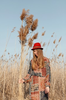 Bohemian woman posing in nature field with dead grass