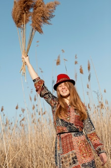 Bohemian woman posing with dead grass