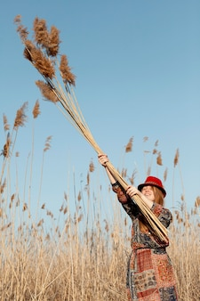 Bohemian woman posing with tall dead grass