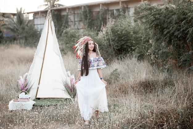 Boho 보헤미안 소녀는 가을 필드에서 인도 맥시 드레스와 보석을 착용 스타일