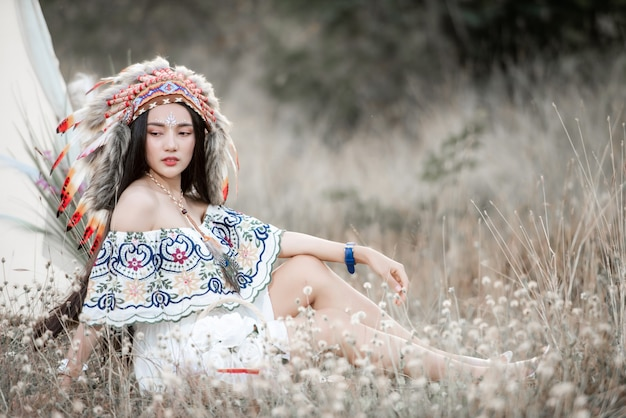 Boho bohemian girl styled wearing indian maxi dress and jewellery in autumn field