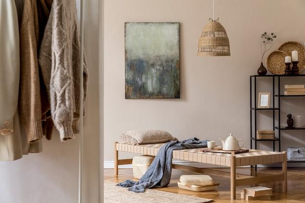 디자인 긴 의자, 베개, 바구니, 그림, 옷걸이, 등나무 자연 장식 및 우아한 개인 액세서리와 함께 거실의 boho 구성.