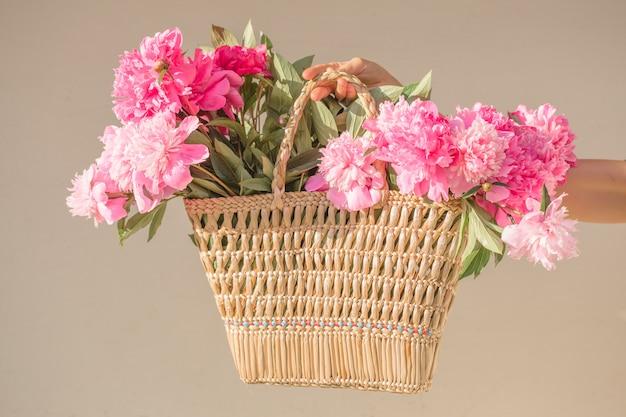 Девушка boho держа розовые пионы в корзине соломы.