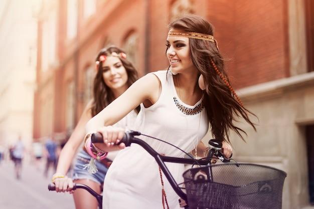 Ragazze boho in sella a una bicicletta in città