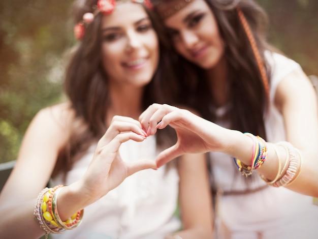 Бохо девушки показывают форму сердца из рук
